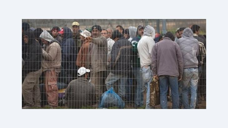Palestinian workers wait for Israeli soldiers to open the gate of a separation barrier between the Jewish settlement of Modiin Elite and the west bank village of Harbeta to return home after the day's work in Israel, 15 March 2012 (photo: Oded Balilty/AP/dapd)