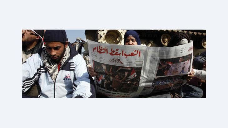 Young Egyptian reading Al-Ahram, one day after Mubarak's fall (photo: AP)