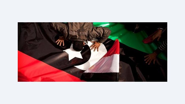 An Egyptian demonstrator on Tahrir Square in Cairo kisses the new Libyan flag out of solidarity with the rebels in Egypt (photo: AP)