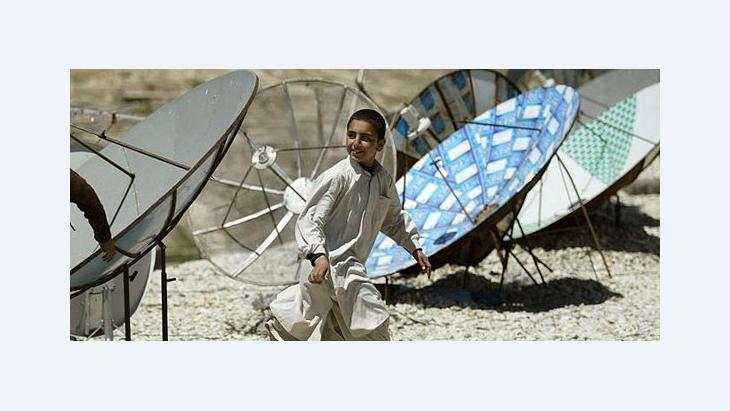 Afghan boy and an array of satellite dishes in Kabul (photo: AP)