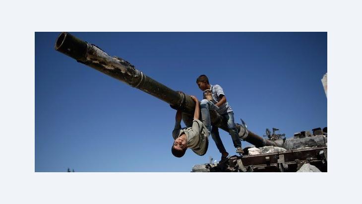 Children playing on a destroyed Syrian tank in Aleppo (photo: AP/Muhammed Muheisen)