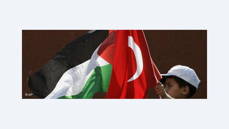 A boy carries the Turkish and the Palestinian flag (photo: AP)