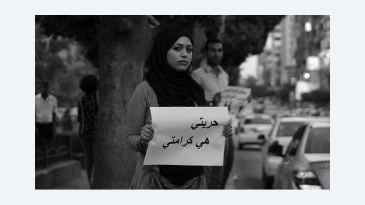 A women demonstrating in Cairo and holding up a sign that reads 'My freedom is my dignity' (photo: AP)