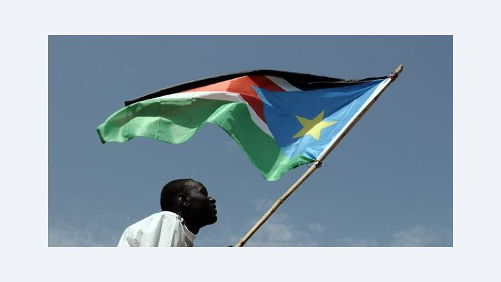 Man holding flag of South Sudan (photo: picture-alliance/dpa)