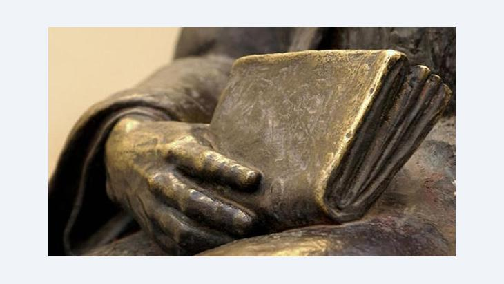 Close-up of a statue of a person holding a book (photo: Bilderbox)