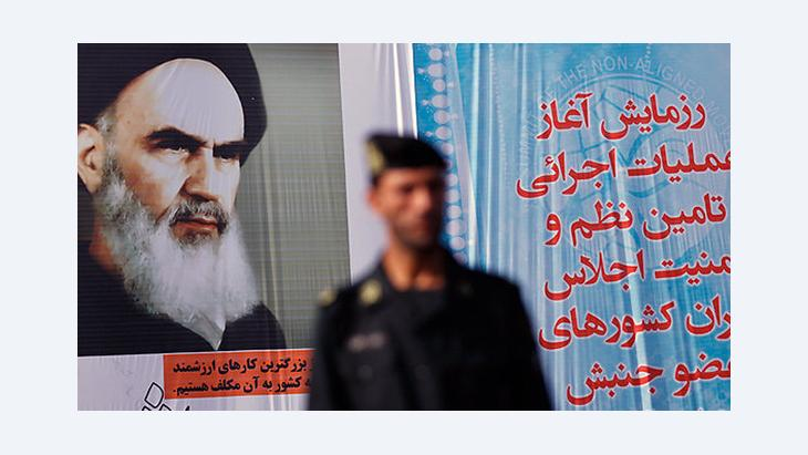 An Iranian police officer standing in front of a poster of the Grand Ayatollah Khomeini in Tehran (photo: mehrnews)