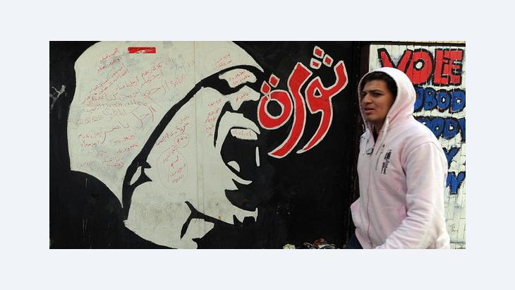 A young man walks past graffiti that reads 'revolution' in downtown Cairo (photo: dpa)