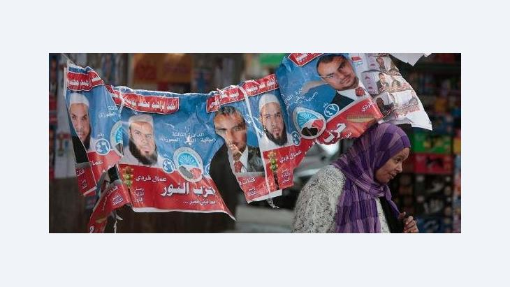 An Egyptian woman passes under electoral posters with pictures of candidates of the Salafist Al-Nour party (photo: AP/dapd)
