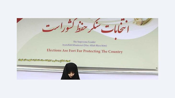 A woman stands in front of a poster declaring that elections in Iran are for the protection of the country (photo: Mehr)