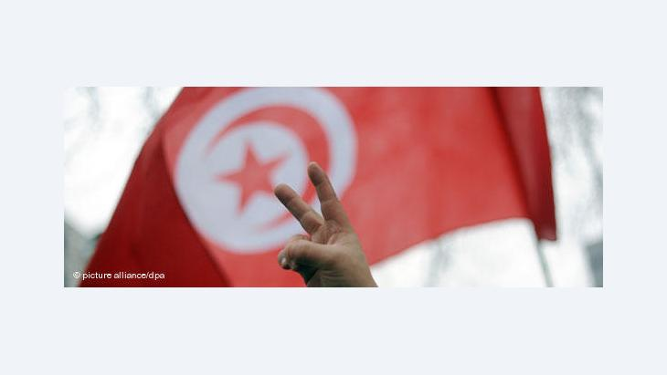 Tunisia's flag and a man showing the victory sign (photo: picture-alliance/dpa)