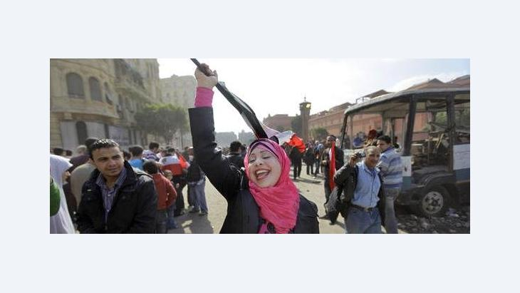 An Egyptian woman sings patriotic songs by herself as she walks along the street outside the Egyptian Museum near Tahrir Square in downtown Cairo, Egypt, Saturday, Feb. 12, 2011 (photo: AP)