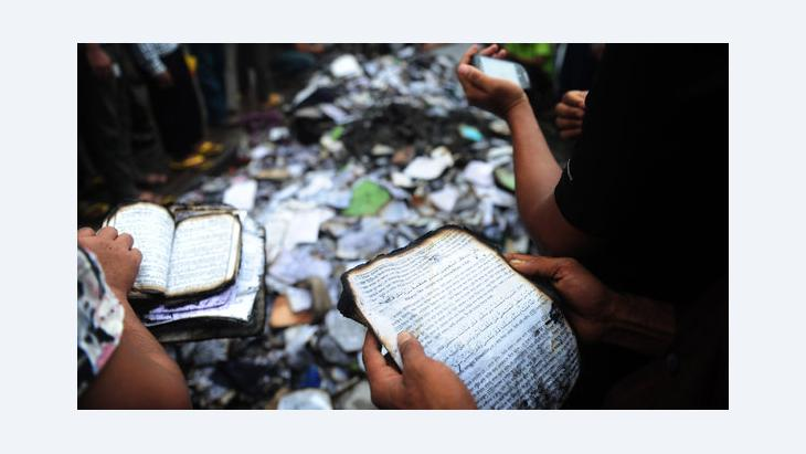 Bangladeshi people look at burnt religious literature, including the Holy Koran, in Dhaka following a clash between police and Islamists, 6 May 2013 (photo: MUNIR UZ ZAMAN/AFP/Getty Images)