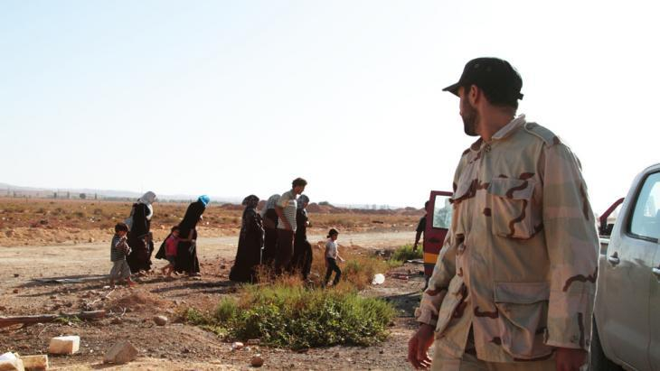 Security official and a refugee family in Libya (photo: Gaia Anderson/DW)