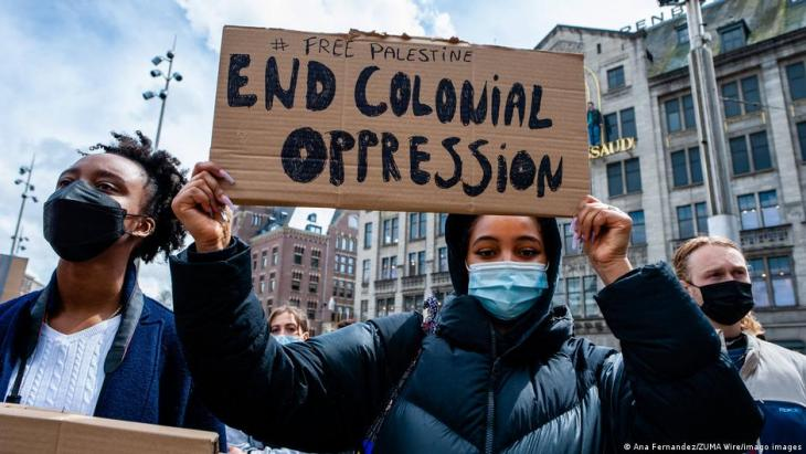 16 May 2021, Amsterdam, Netherlands: a Black woman seen holding a placard over her head against colonialism during a demonstration. In Amsterdam thousands of Dutch people gathered at the Dam Square in Amsterdam to condemn the Israeli attacks and the forced evictions of Palestinians from Sheikh Jarrah neighbourhood in occupied East Jerusalem.