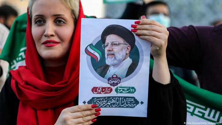 A woman holds a picture of Iran's newly-elected president Ebrahim Raisi as supporters celebrate his victory in Imam Hussein square in the capital Tehran on 19 June 2021.