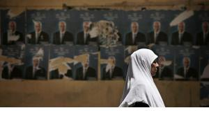 An Egyptian woman walks past election posters for the upcoming elections in Cairo (photo:AP)