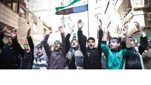 Young men and youths demonstrating against the Assad regime in the area of al Qaterji, north-east of Aleppo, waving the flag of the Free Syrian Army (photo: dpa)