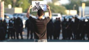 Riot police watch as an Bahraini anti-government protester holds up a picture of jailed political leader Hassan Mushaima with the words 'Mushaima is in danger', during a protest in Diraz, Bahrain, on Friday, Nov. 2, 2012 (photo: Hasan Jamali/AP/dapd)