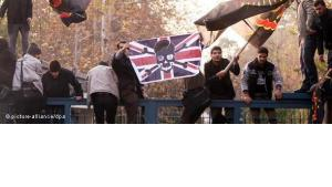 Members of the Basij militia waving anti-British flags as they storm the British embassy in Tehran (photo: dapd)