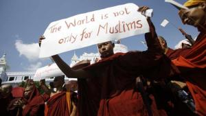 A Myanmar Buddhist monk holds a sign saying 'The world is not only for Muslims' as he takes part in a demonstration against the Organisation of the Islamic Conference in Yangon on October 15, 2012 (photo: AFP PHOTO/Ye Aung Thu)