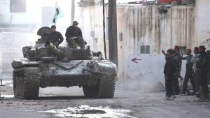 Fighters of the Free Syrian Army driving in a tank through a street near Damascus (photo: Reuters)