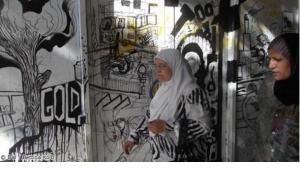Two women and a graffiti (photo: DW / Bettina Kolb)
