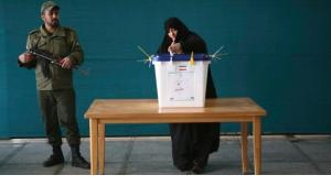 A woman casting her vote in Tehran, a military soldier with machine gun standing guard (photo: Reuters)
