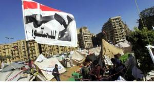 Anti-Mursi protesters sit outside their tents, below a flag that reads, ''No to the Constitution'' at Tahrir Square in Cairo, 10 December 2012 (photo: Reuters)