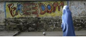A woman wearing Burqa walking in front of 'freedom' graffiti (photo: AP)