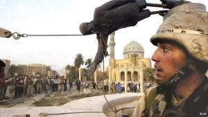 Iraqi civilians and U.S. soldiers pull down a statue of Saddam Hussein in downtown Baghdad, 9 April 2003 (photo: AP/Jerome Delay)