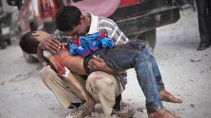 A Syrian man holds the body of his son, killed by the Syrian Army (photo: AP)