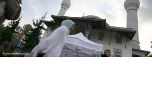 Muslims pass by the Sehitlik Mosque in Berlin (photo: picture alliance/dpa)