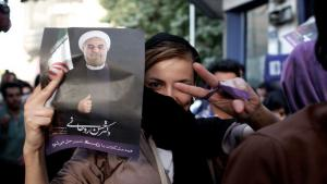 An Iranian woman flashes the sign for victory as she holds a portrait of Hassan Rouhani during celebrations after he won the Islamic Republic's presidential elections in Tehran on 15 June 2013 (photo: Behrouz Mehri/AFP/Getty Images)