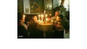 Worshippers light candles in the Church of the Nativity in the West Bank town of Bethlehem Friday Dec. 23, 2005 (photo: AP)