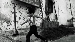 A young girl runs past a wall at the corner with Tripoli street, in Misrata, which was damaged by shelling during the Libyan uprising in 2011. Misrata offered fierce resistance to the ex-regime's army and was consequently one of the most heavily hit cities in the country during the war. Signs of pride and joy offer a stark contrast to the scarred streets of Misrata these days.