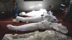 A man sits next to a row of corpses of members of the Muslim Brotherhood (photo: Reuters/Amr Abdallah Dalsh)