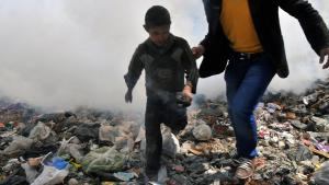 A boy and a man run away from a cloud of gas in Aleppo, 24 March 2013 (photo: Bulent Kilic/AFP/Getty Images)