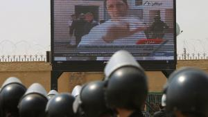 Egyptian riot police look up as they watch Alaa, the son of ousted president Hosni Mubarak, seen on a large TV screen erected outside the Cairo criminal court, as he reaches out to cover the lens of a TV camera during his arrival for his trial along side his father and brother accused of corruption and murder on August 15, 2011 (photo: Khaled Desouki/AFP/Getty Images)