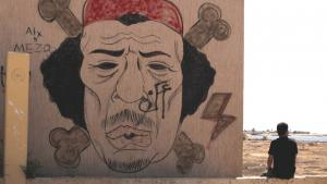 A Libyan man sits near a mocking graffiti of al-Gaddhafi, in Benghazi, Libya (photo: AP)