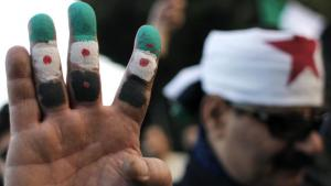 An anti-Syrian regime protester holds up his fingers painted in revolutionary flag colors during a protest outside the Arab League headquarters in Cairo, Egypt Sunday, Jan. 22, 2012 (photo: Nasser Nasser/AP/dapd)