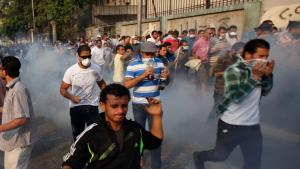 Supporters of disempowered president Morsi Mursi flee from riot police using tear gas (photo: Reuters)