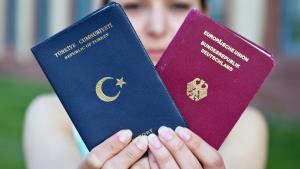 A woman holding two passports, one German, and one Turkish (photo: picture-alliance/dpa)