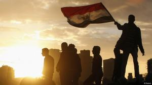With a dramatic sunset backdrop illumating the scene from behind, a protestor stands on a ledge above his friends and waves the red, white and black Egyptian flag through the sunlight (photo: REUTERS/Mohamed Abd El Ghany)