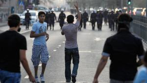 An anti-government protester gestures towards riot police during clashes in the village of Sanabis west of Manama, November 6, 2012. Hundreds of protesters march on the street of the village defying the ban on protests set by Bahrain's Ministy of Interior (photo: Reuters)