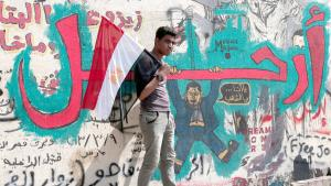 A young Egyptian carrying an Egyptian flag and standing in front of some anti-Morsi graffiti in Cairo (photo: picture-alliance/dpa)