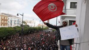 A man holds up a Tunisian flag and a placard calling for Ben Ali to step down, Tunis, 2011 (photo: picture-alliance/dpa)