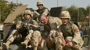 American troops evacuating a badly wounded female American soldier on the hood of a Humvee from a Baghdad police station after the station was attacked by rockets fired from an apartment building across the street, 25 May 2004, Baghdad, Iraq (photo: Michael Kamber)