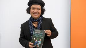 """The Indonesian writer Andrea Hirata poses with the German translation of his book """"The Rainbow Troops"""" (photo: picture-alliance/dpa)"""