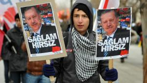 """An opponent of the AKP government holds up two posters of Prime Minister Erdogan with the slogan """"Big thief"""" (photo: Reuters)"""