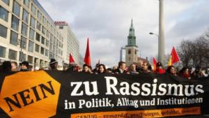 """Protesters at a demonstration in Hamburg walk behind a very large banner that reads """"NO to racism in politics, everyday life and institutions. ENOUGH killing, silence, tolerance, cover-ups"""" (photo: dpa)"""